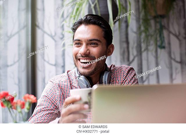 Man laughing and drinking coffee at laptop in cafe