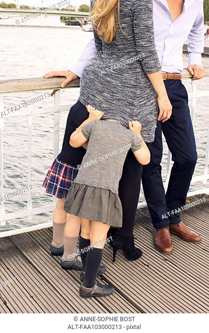 Family together outdoors, little girls hiding under mother's sweater