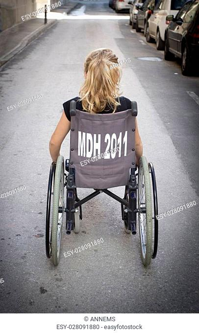 A girl sitting in a wheelchair with her back to the camera