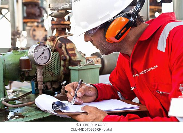 Worker noting gauge at oil refinery