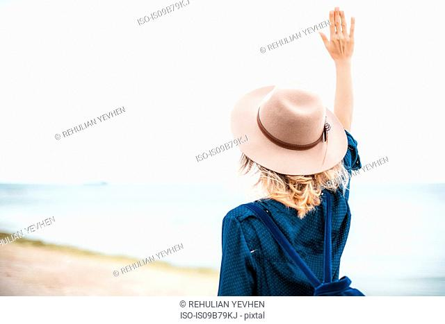Mid adult woman standing on beach, hand in air, rear view