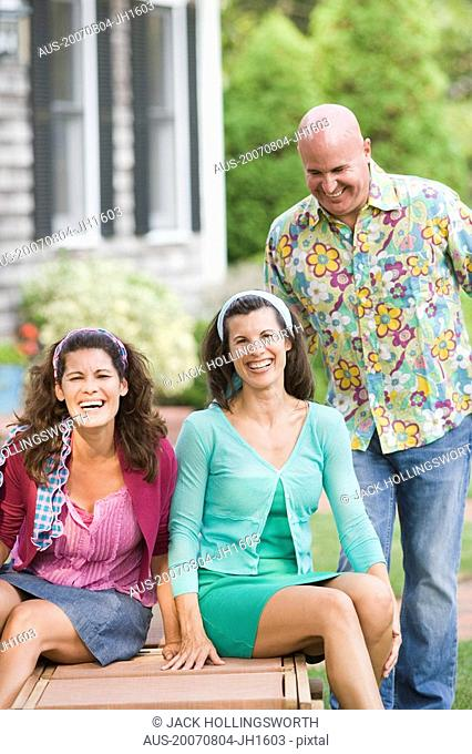 Two mature women sitting on a lounge chair with a mature man standing beside them
