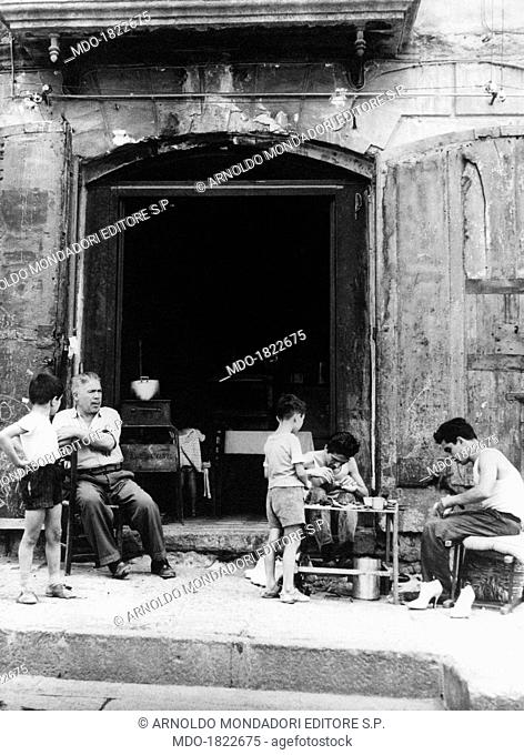 Some people doing craft jobs in the street in front of the entrance of a house in via Roma, today via Toledo. Naples, 1950s