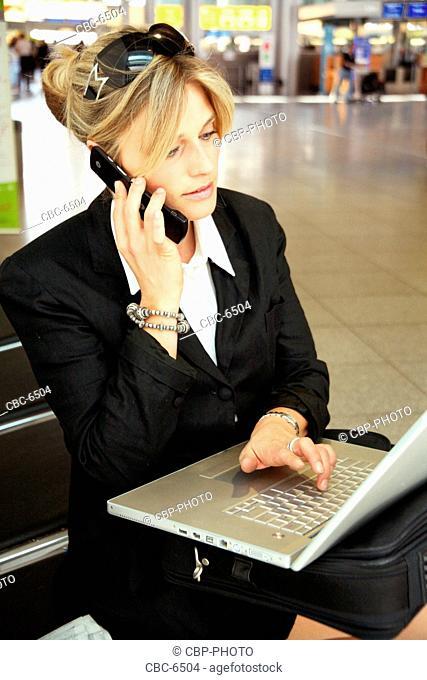 Young Businesswoman Using Laptop And Cellphone At The Airport