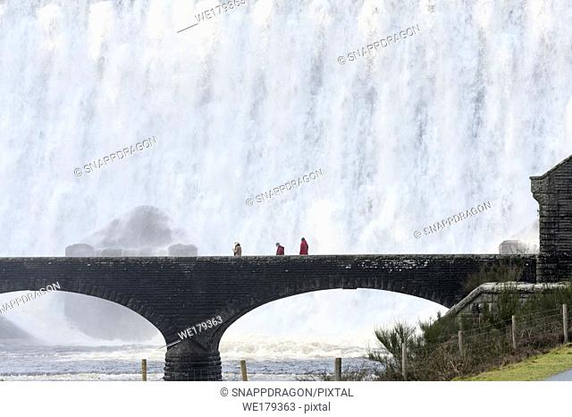 Elan Valley, Powys, Wales, UK. Visitors walk across a bridge as water cascades over the Caban-coch dam, at Elan Valley village near Rhayader in Powys, Wales, UK