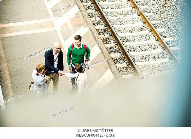 Businesspeople shaking hands on railway platform