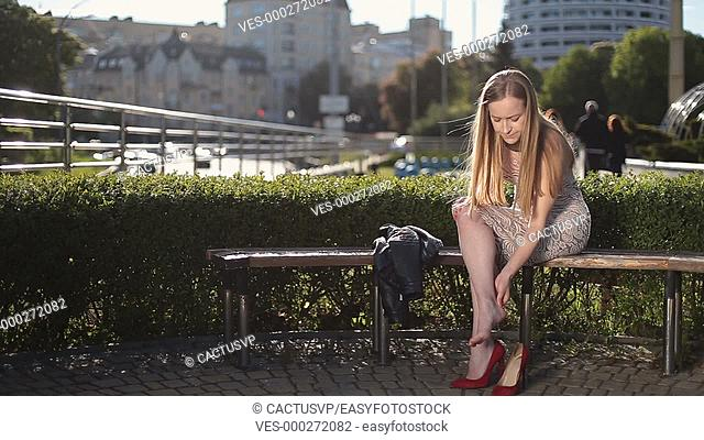 Charming woman in high heels massaging tired legs