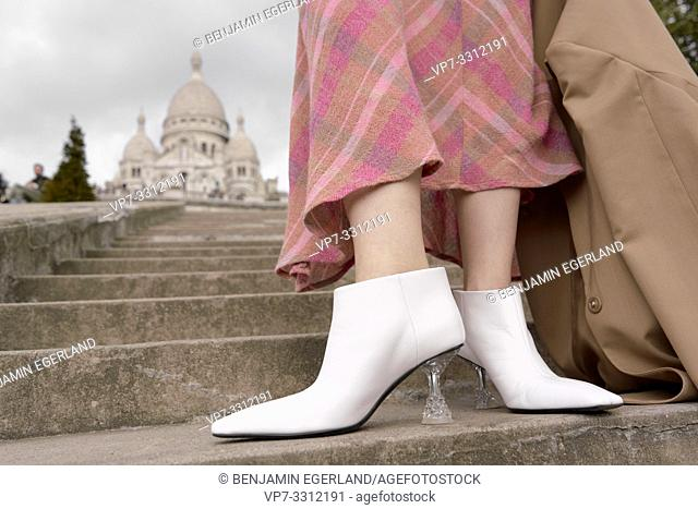 stylish shoes of fashionable blogger woman in front of touristic sight Basilica Sacré-Cœur, white high heels, during fashion week, in city Paris, France