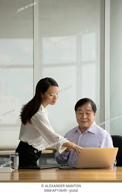 Singapore, Two business people talking at desk in office