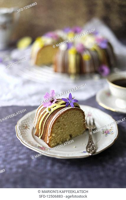 A guglhupf with yellow and white icing and edible flowers