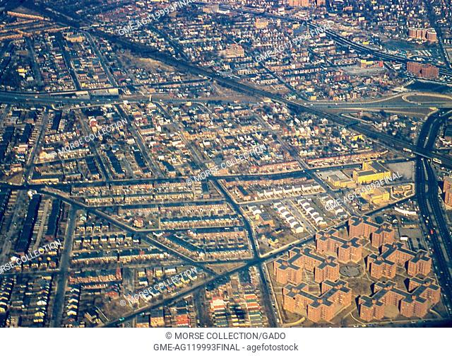 Aerial view facing north of the neighborhoods of Middle Village, Rego Park, and Elmhurst, Queens, New York City, 1957. The Long Island Rail Road (LIRR) train...