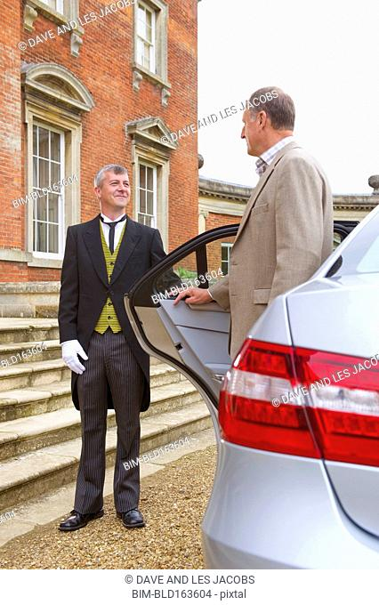 Caucasian butler opening car door for man