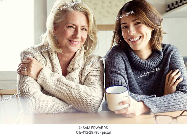 Portrait smiling mother and daughter in sweaters drinking coffee in kitchen