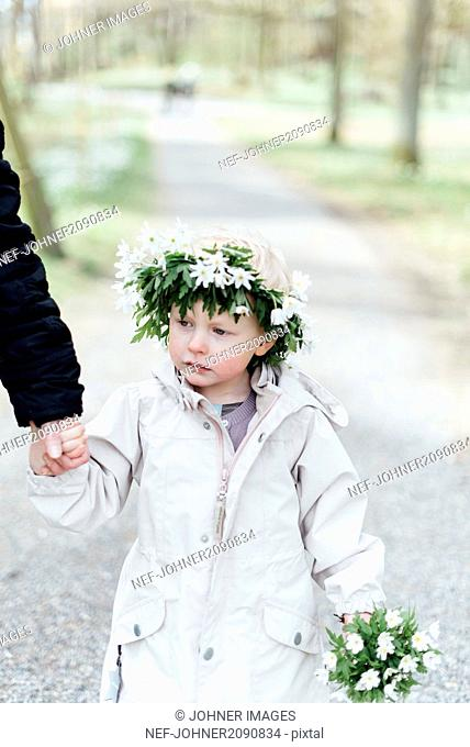 Girl wearing anemone wreath holding parents hand
