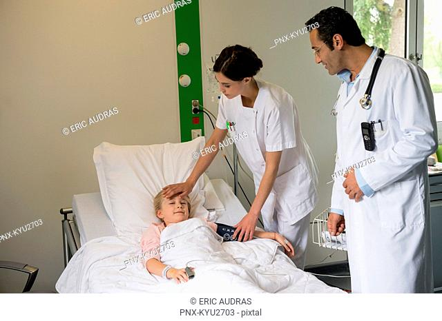 Medical attendants examining to a girl patient in hospital bed