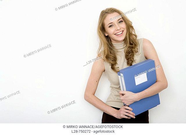 Businesswoman holding file folders, smiling, portrait