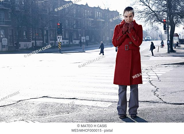 Woman wearing red coat standing at crossroad in gray city
