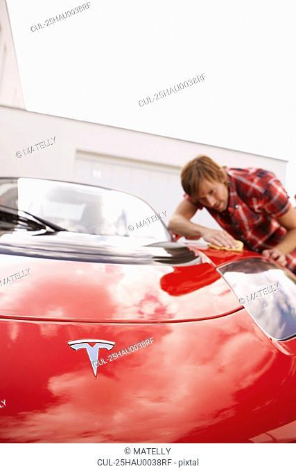 Man proudly polishing hi electric car
