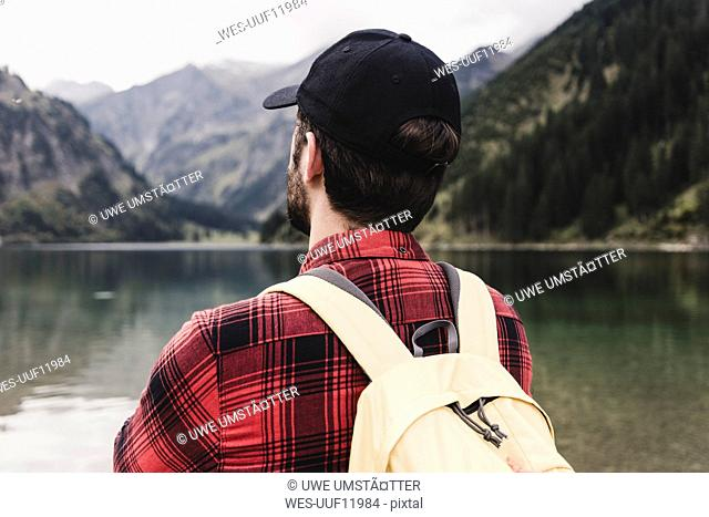 Austria, Tyrol, Alps, rear view of hiker at mountain lake
