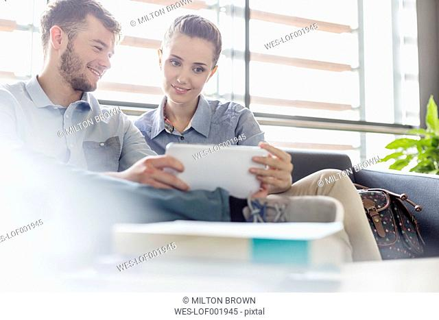 Smiling young man and woman sharing digital tablet on couch