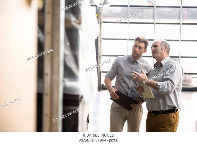 Two men talking in factory warehouse