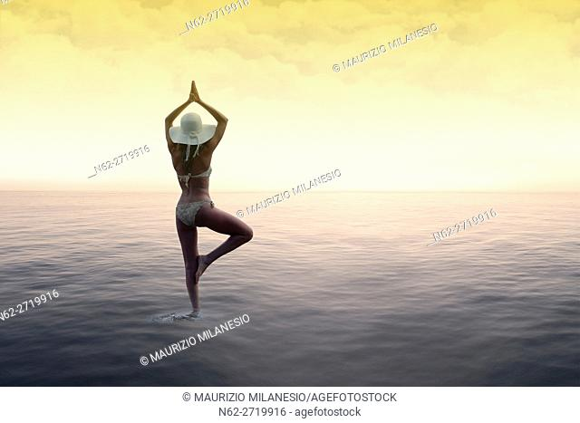 Woman with a white hat standing on the water in the sun salutation yoga pose, on background sky with colored clouds by a warm sunset