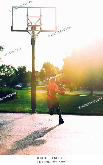 Young boy on basketball court, holding basketball, mid layup, rear view