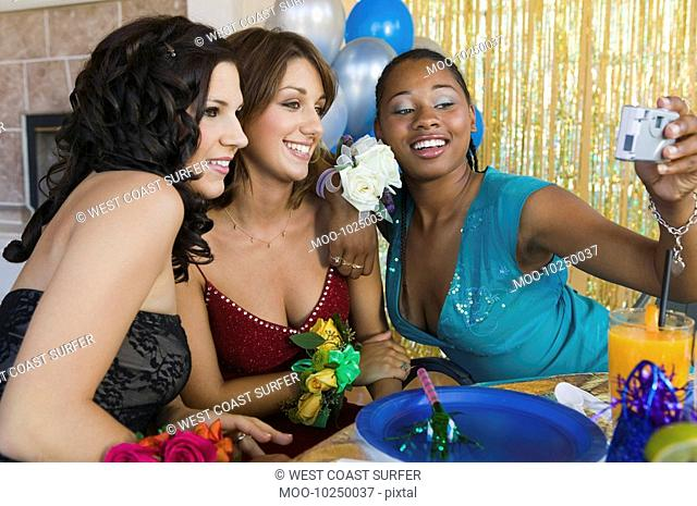 Well-dressed teenage girls taking picture at school dance