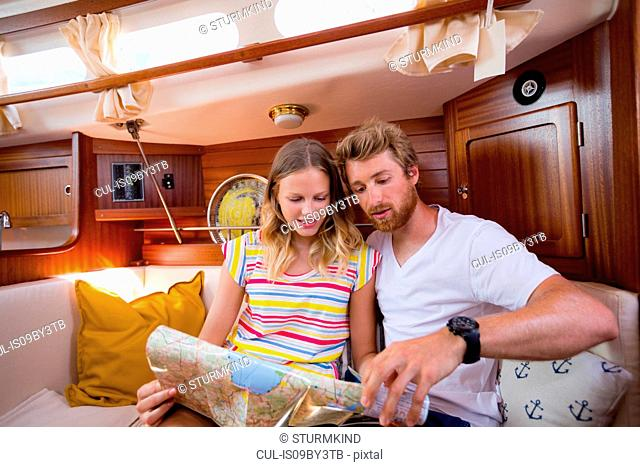 Young couple in sailboat cabin looking at folding map