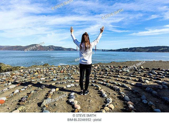 Caucasian woman standing in circle of rocks near ocean