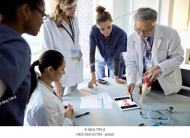 Doctors with model using digital tablet in meeting