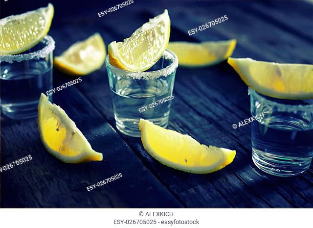 stack with transparent alcohol and lemon slices on the texture wooden background