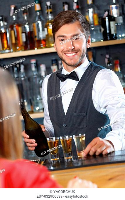 Portrait of a handsome bartender standing at the counter smiling and holding a shot glass looking at a woman sitting back to us