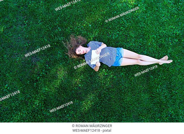 Young woman lying on grass, holding digital tablet
