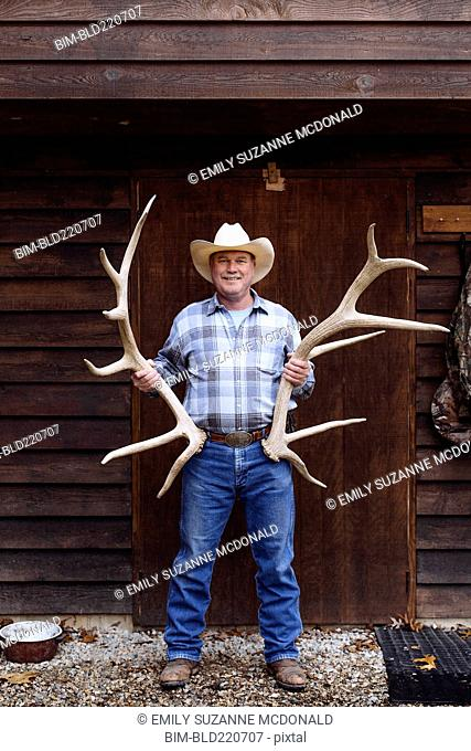 Caucasian farmer holding antlers on front porch