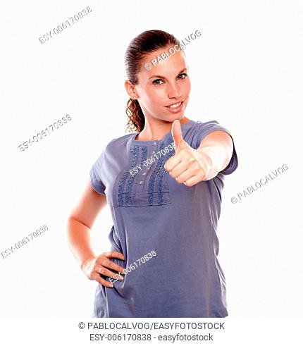 Positive young woman lifting the fingers up looking at you against white background