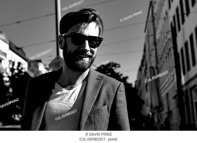 Portrait of man wearing blazer and sunglasses smiling, Berlin, Germany
