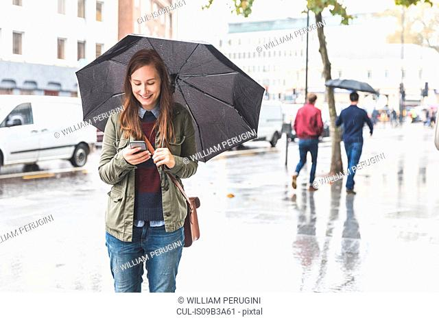 Young standing in street, carrying umbrella, using smartphone