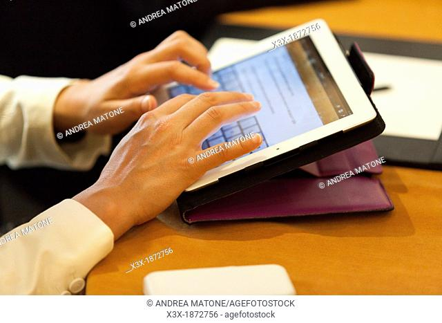 Person typing on a tablet during a business meeting