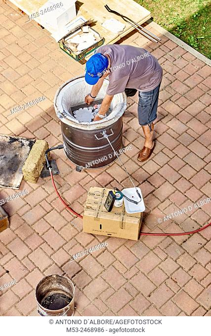 A person placing ceramic objects inside a gas firing kiln, ready for the heating process
