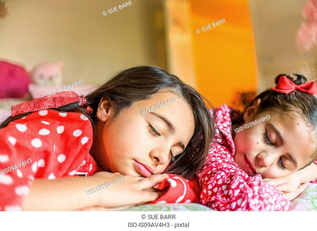 Two sisters sleeping on bed