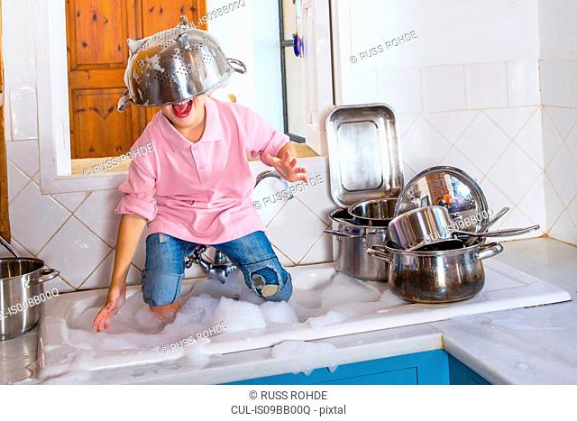 Boy playing in kitchen sink with colander on his head