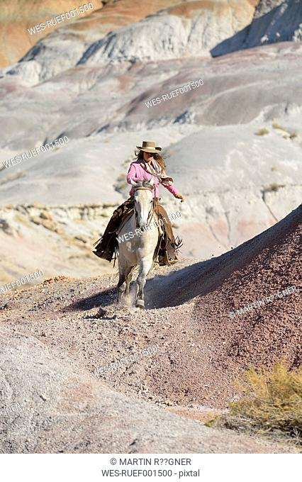 USA, Wyoming, cowgirl riding in badlands