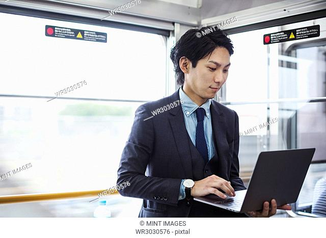 Businessman wearing suit standing on a commuter train, holding laptop