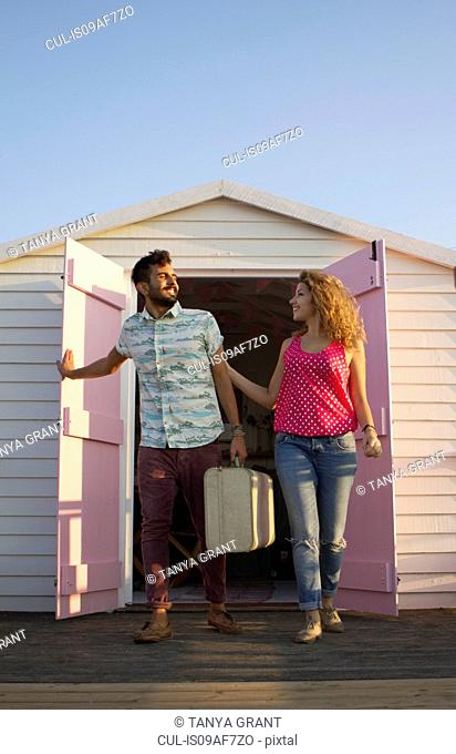 Young couple leaving beach hut with suitcase