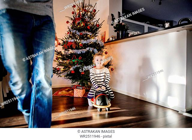 Girl playing with toy car against decorated Christmas tree at home