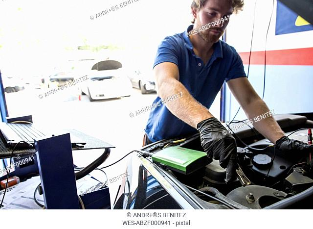 Mechanic placing a battery clip in a car