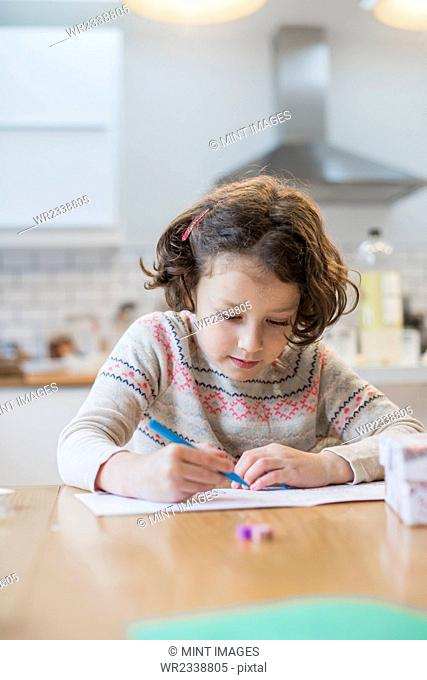A girl sitting at a kitchen table writing a card or letter