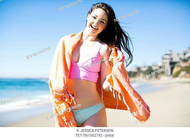 USA, California, Woman standing by sea on Laguna Beach