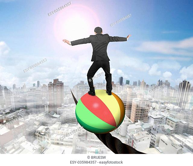 Businessman standing on top of colorful ball, balancing on a wire, with sun mist cityscape background